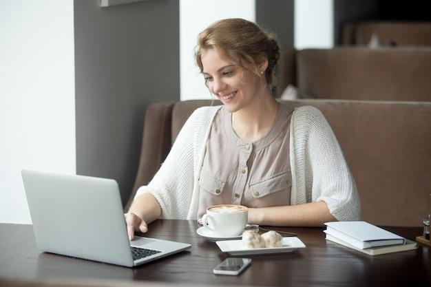 カフェ、ラップトップを使用して、幸せな女性の半分の肖像画 無料写真