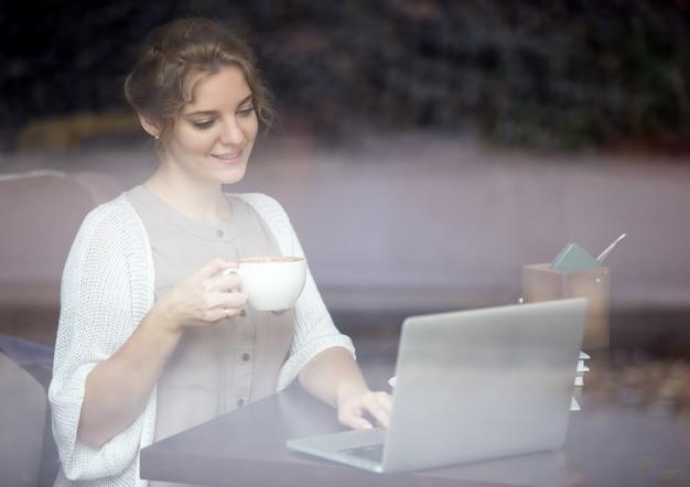 コーヒーショップでラップトップで働く現代の女性。ショットウインドウ 無料写真