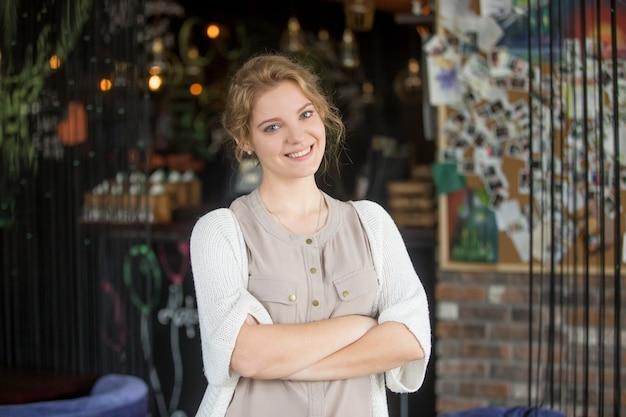 彼女自身のコーヒーショップでポーズをとっている幸せなビジネス女性を笑顔 無料写真