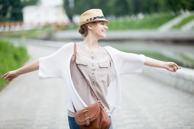 彼女の旅行を楽しむ麦わら帽子の若い楽しい幸せな旅行者の女性 無料写真