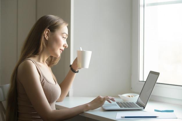 Профиль портрет женщины с ноутбуком на подоконнике Бесплатные Фотографии