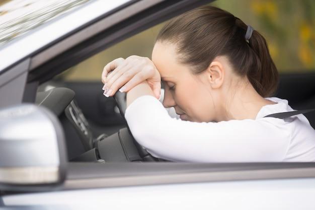 車を運転している彼女の電話で話す若い女性 無料写真