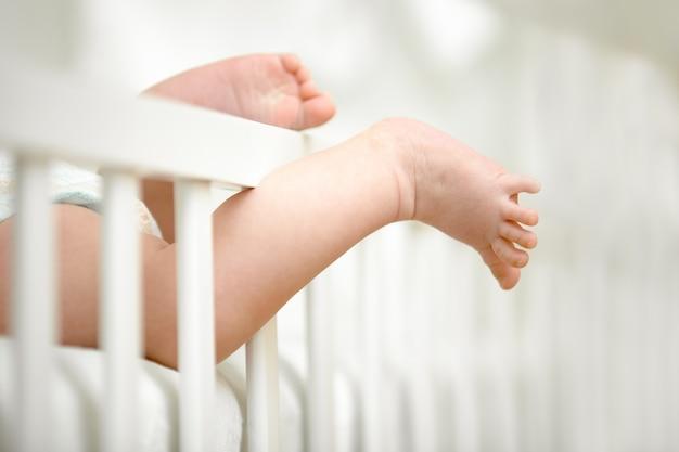 小さな脚がベビーベッドのフレームの間に挟まれている 無料写真