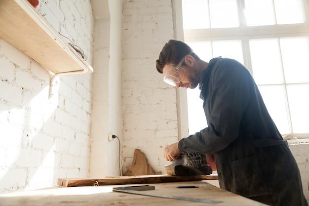 ジョイナーはワークショップで木製の板を磨く 無料写真