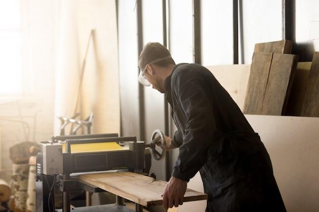 Работник работает стационарный строгальный станок, обрабатывающий деревянную доску с машиной Бесплатные Фотографии