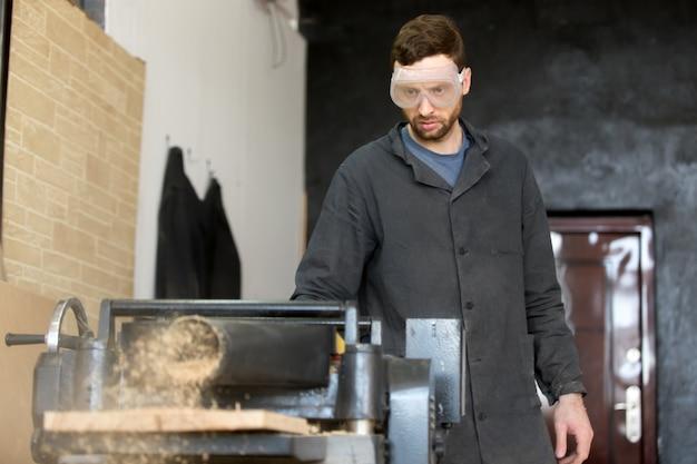 Карпентер в защитных очках работает на станке Бесплатные Фотографии