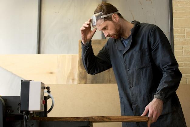 工作機械で製材工場で働く若い大工 無料写真