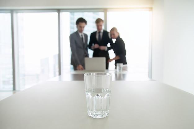 オフィスの机の上の水のガラスのクローズアップ 無料写真