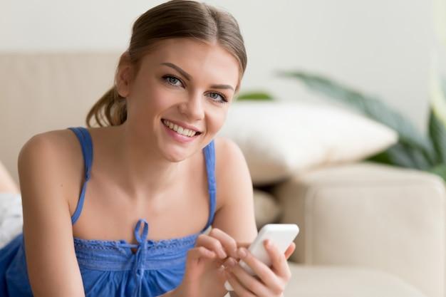 女性が自宅で休んでいる間携帯電話を使用して 無料写真