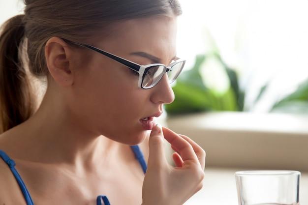 丸い白い錠剤を飲み込む病気の女性 無料写真