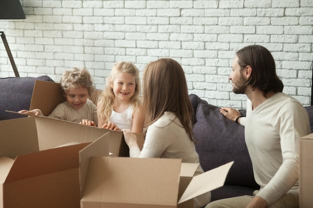 リビングルームで開梱梱包で遊ぶ子供たちと幸せな親 無料写真
