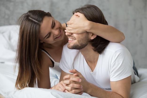 Любящая женщина закрывает глаза мужчины с руками, играя в постели Бесплатные Фотографии