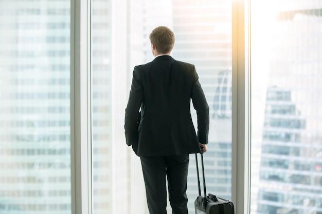 窓の近くのスーツケースと一緒に立っている実業家 無料写真