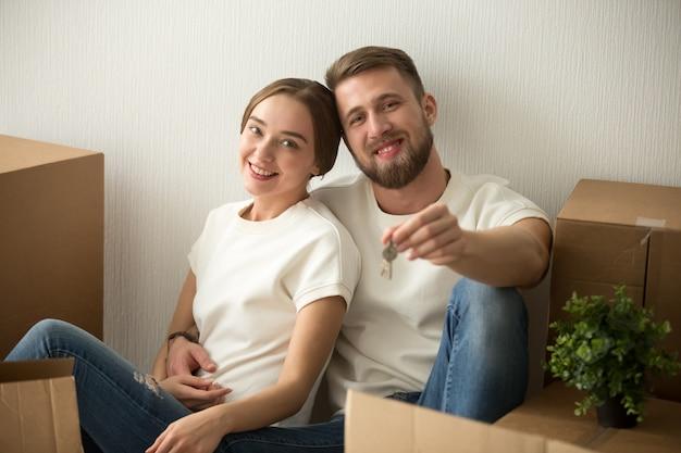 一緒に移動するのに興奮してキーを保持しているカップルの肖像画 無料写真