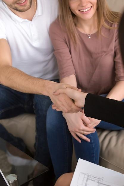 全米リアルター協会加入者と握手するカップル。不動産および家の改修 無料写真