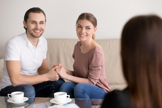 相談に陽気な若い家族カップル。手を繋いでいると笑顔 無料写真