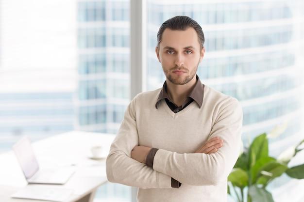 カメラ目線のオフィスに立っている深刻な成功した青年実業家 無料写真