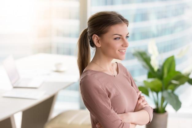 物思いにふける笑顔若い女性窓を見て、腕を組んで、屋内 無料写真