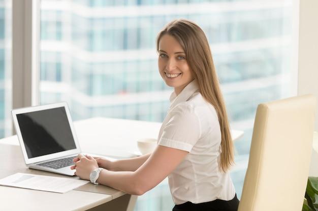 幸せな若い女性起業家のオフィスで働いています。 無料写真