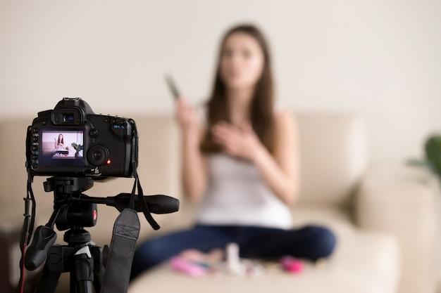 Молодой женский видеоблогер записи продукта обзор для блога. Бесплатные Фотографии