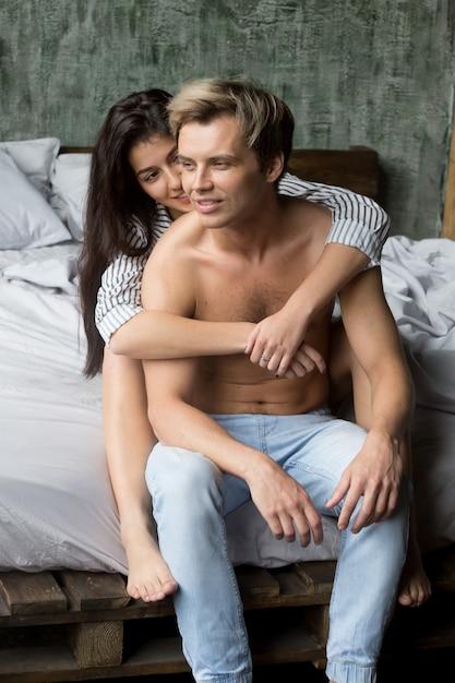 Молодая любящая девушка обнимает сексуальный мужчина, сидя на кровати вместе Бесплатные Фотографии