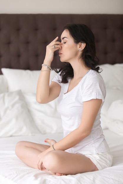 Молодая привлекательная женщина делает позу альтернативного ноздри дыхание на Бесплатные Фотографии