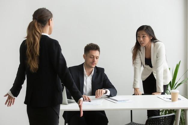 多様性のある同僚がオフィスで時間厳守または期限を逃したことについて議論 無料写真