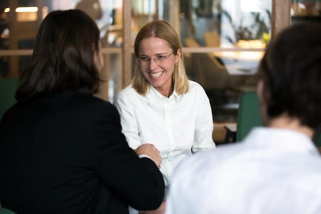 Улыбается бизнесвумен, пожимая руку бизнесмена на переговорах или интервью Бесплатные Фотографии
