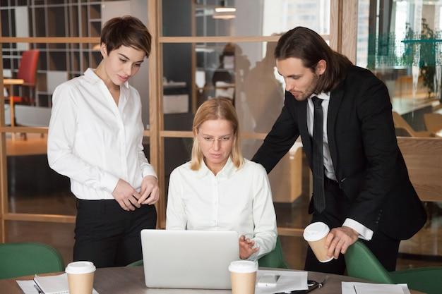 オフィスで一緒にオンラインのタスクを議論する深刻な集中ビジネスチーム 無料写真