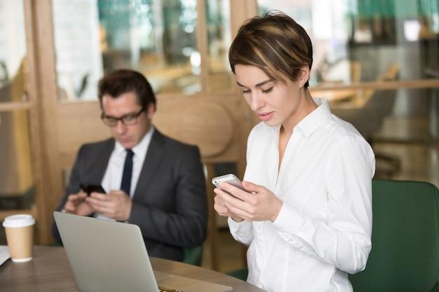 実業家と実業家のオフィスで仕事に携帯電話を使用して 無料写真