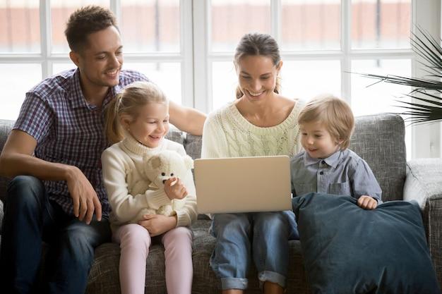 ソファーでラップトップを使用して楽しんで子供たちと幸せな家庭 無料写真