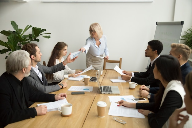 チーム会議でマネージャーに財務報告を渡す上級の実業家 無料写真