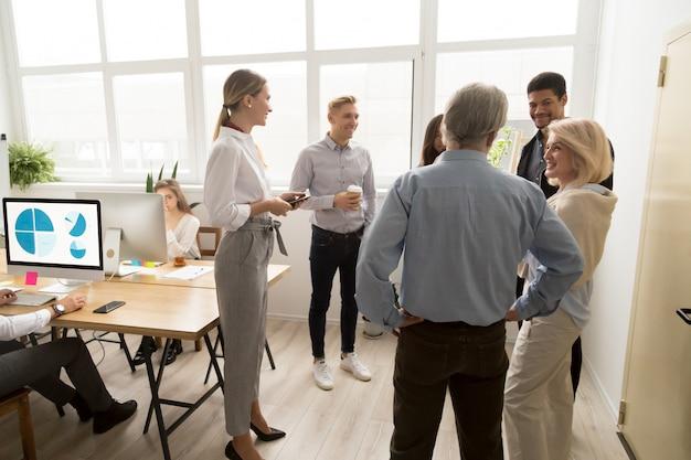 Улыбающиеся счастливые молодые и старшие офисные работники говорят в коворкинг Бесплатные Фотографии
