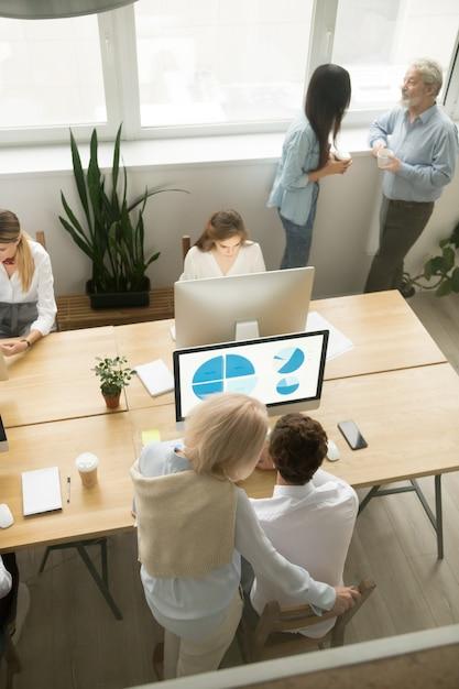シニアと若い従業員のオフィスでは、垂直方向のトップビュー 無料写真