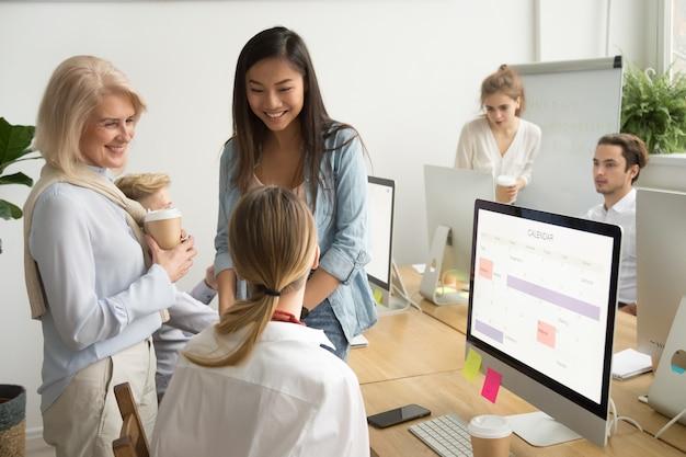 オフィスで話しているさまざまな年齢の多民族のビジネスウーマンの同僚の笑顔 無料写真