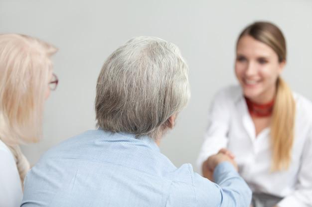 年配のカップルハンドシェイクアドバイザーまたは医療従事者の背面図 無料写真