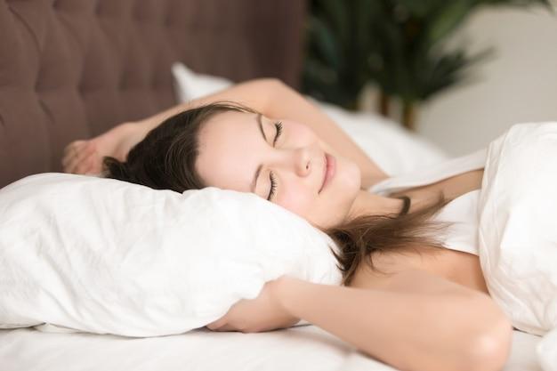 Милая молодая женщина наслаждается длинным сном в кровати Бесплатные Фотографии