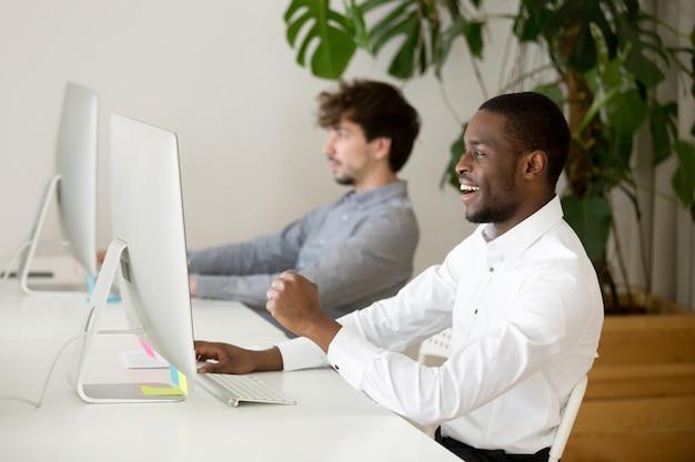 オンラインでの勝利または良い結果に興奮して幸せな黒人の従業員 無料写真
