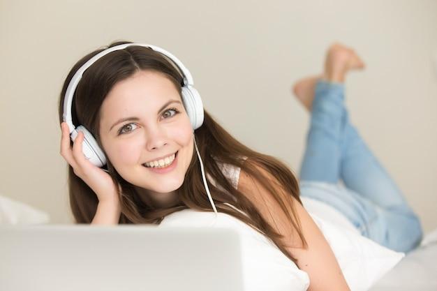 オンラインで新しい音楽を聴いて楽しんでいるかわいい十代の少女 無料写真