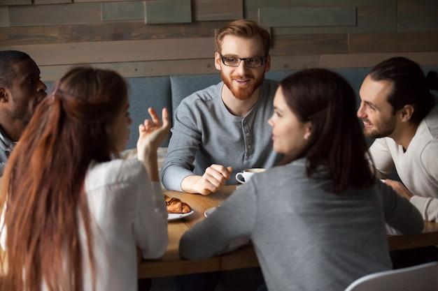 多様な若者が話しているとカフェで一緒に楽しんで 無料写真