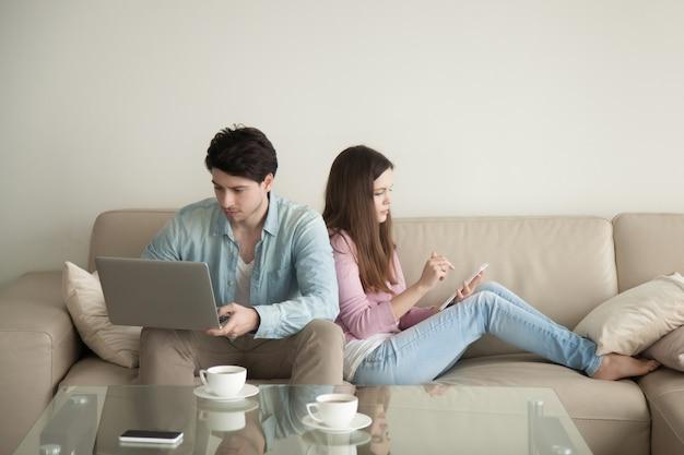 Молодой мужчина и женщина спиной к спине, используя ноутбук Бесплатные Фотографии