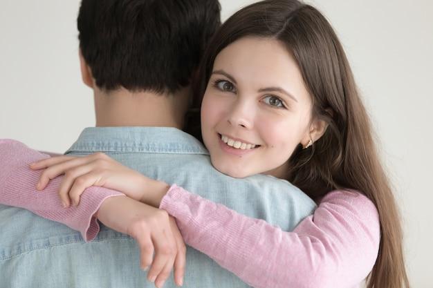 Портрет молодой счастливой улыбающейся женщины, обнимающей мужчину с любовью Бесплатные Фотографии