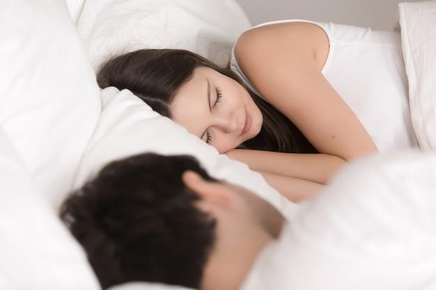 Молодая прекрасная красивая пара удобно спать в постели, рядом Бесплатные Фотографии