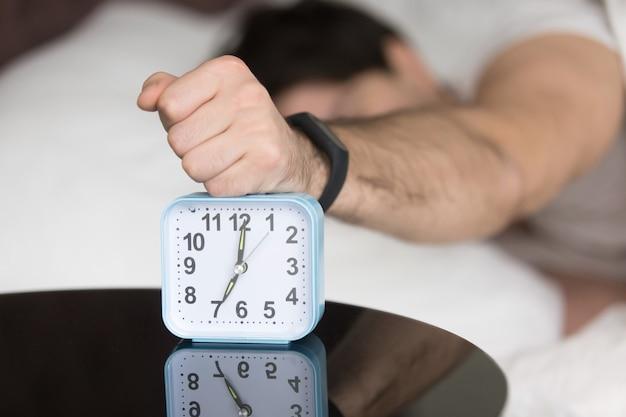 Злой сонный молодой парень выключает шумный надоедливый будильник Бесплатные Фотографии