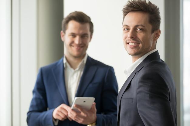 カメラを見て笑顔の青年実業家、アプリケーション開発 無料写真