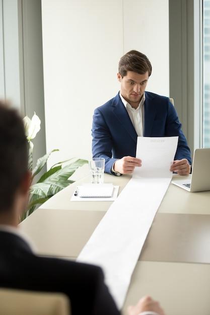 Менеджер по персоналу читает слишком длинные резюме кандидатов Бесплатные Фотографии