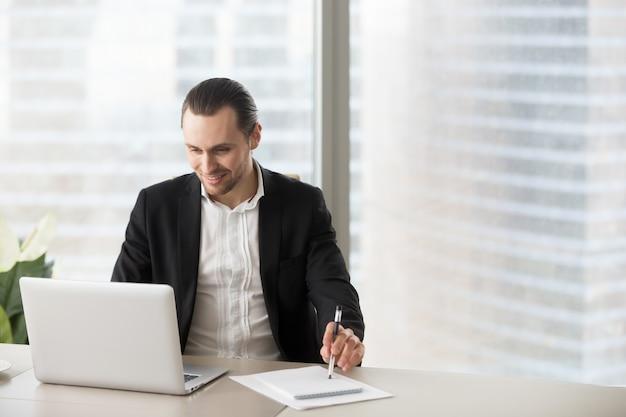 ノートパソコンの画面を見てオフィスで幸せな笑みを浮かべて実業家。 無料写真