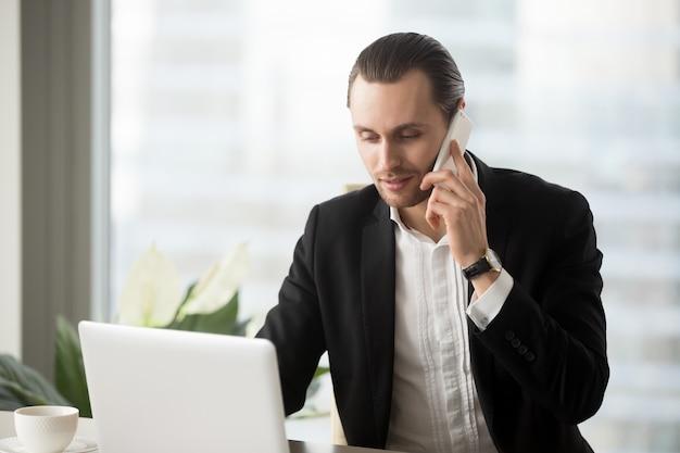 ノートパソコンを見てオフィスの若いビジネスマン 無料写真