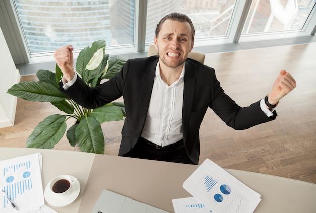 成果を祝う机で幸せなビジネスマン 無料写真