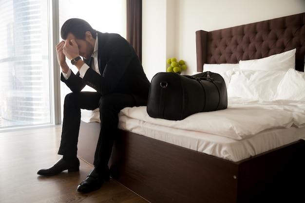 Разочарованный человек в костюме, сидя на кровати, кроме багажа мешок. Бесплатные Фотографии